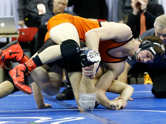 Oconto Falls' Nate Trepanier, top, wrestles with Wrightstown's Ben Klister during their Division 2 state championship match Feb. 27 at the Kohl Center in Madison.