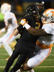 Missouri's Drew Lock is tackled by Kahlil McKenzie