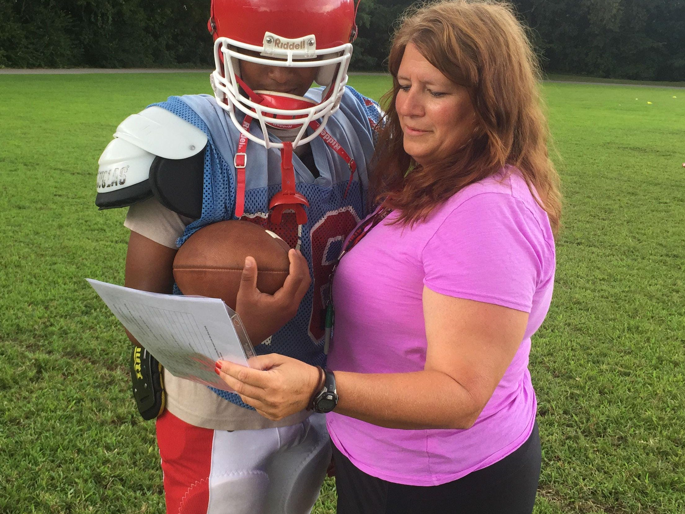 Glencliff quarterback Varon Solano consults with Colts assistant coach Lisa Limper.