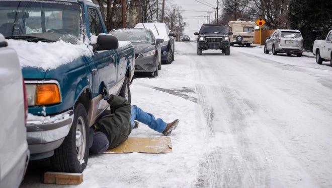 """Stephan Barker lends a helping hand as he crawls under a strangers truck to help put it in gear in Nashville, Tenn., Wednesday, Jan. 17, 2018. """" Everything breaks out in the cold weather,"""" says Barker."""