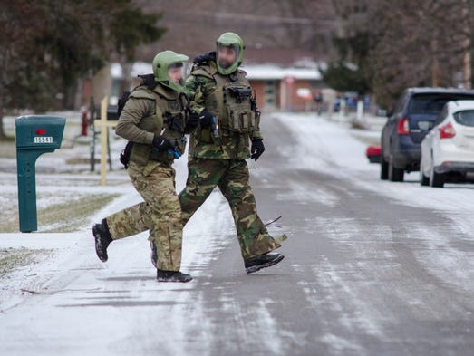 Team officers run across Auburndale to take cover behind
