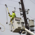 A Gulf Power worker repairs a downed power line caused by wind gusts at the corner of Main Street and Barrancas Avenue.