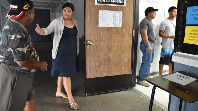 Juliet San Nicolas, precinct official at Inarajan Middle School, invites Inarajan resident Tony Duenas to cast his ballot on Nov. 8.