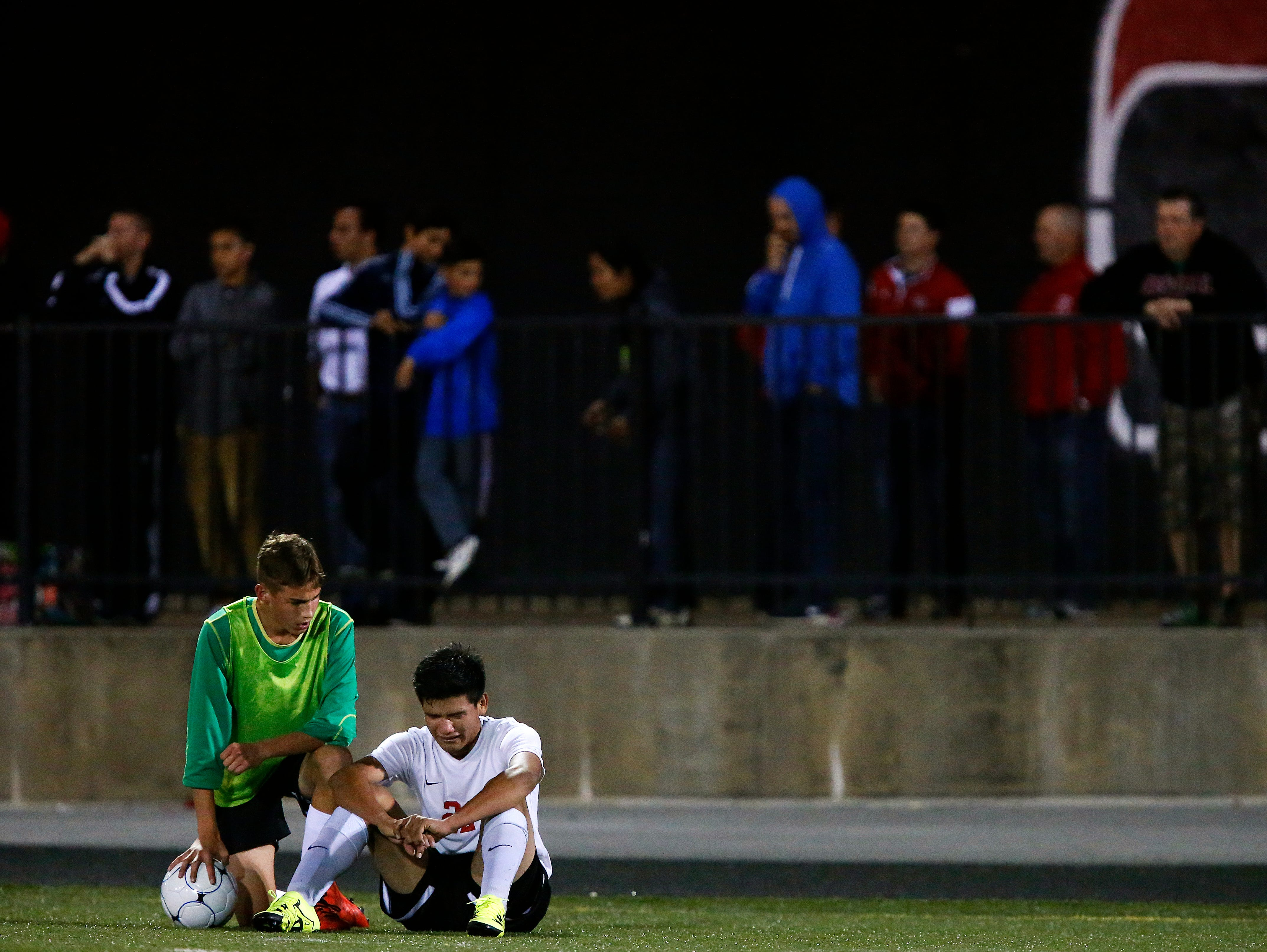 Central High School forward Oscar Leiva (22) is consoled by a teammate after the Bulldogs sectional playoff game against the Nixa Eagles at Harrison Stadium in Springfield, Mo. on Nov. 3, 2015. Nixa won the game 1-0 and kicked Central off of the playoffs.