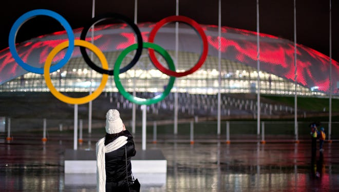 Andreevna Mariya Smorodskaya, a make-up artist for the opening ceremonies, takes a photo of the Olympic rings against the Bolshoy Ice Dome during a roof light display of moving flames on Friday in Sochi, Russia.