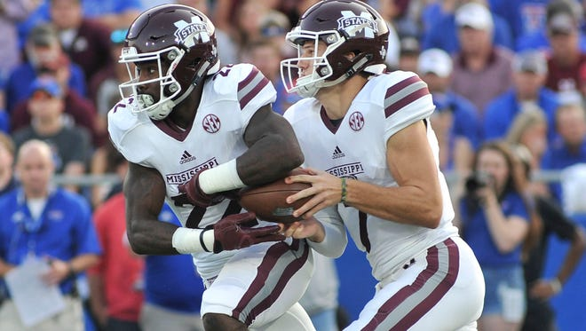 Nick Fitzgerald (7) hands the ball off to running back Aeris Williams (22) during the first half against the Louisiana Tech Bulldogs.