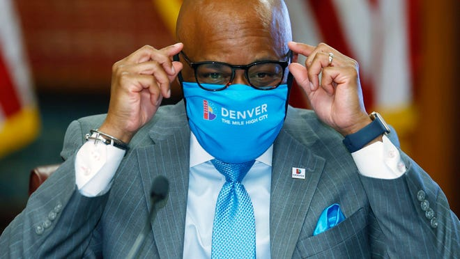 Denver Mayor Michael Hancock adjusts his glasses after putting on his face mask after a news conference Tuesday to explain the city's plan to allow businesses to reopen later this week.