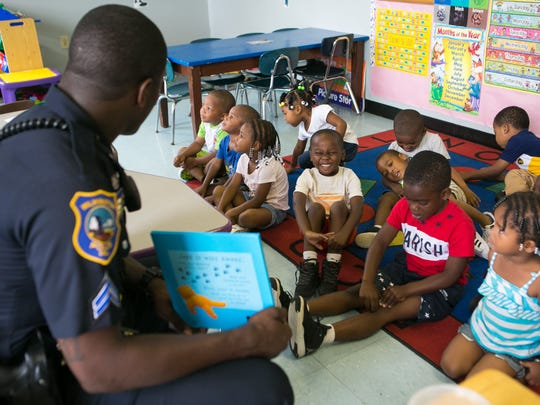 Wilmington Police Officer Michael Spencer reads to the children at Our Future Christian Childcare Center. The findings of a study into the Wilmington Police Department were released Tuesday.