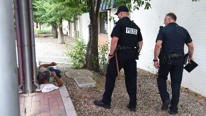 Police officers Nick Rogers and Trevor Smotherman check on a man resting behind a Max bus stop on Mason Street in Old Town Fort Collins on Thursday, June 30, 2016. Fort Collins police have started using bike patrols in recent weeks to address the surge in homeless and transient related calls in the city.