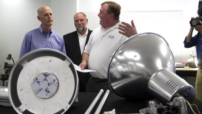 Gov. Rick Scott learns about the lighting products at Global Tech LED from Jeffrey Newman, center, and Gary Mart in Bonita Springs on Thursday during a campain stop there.
