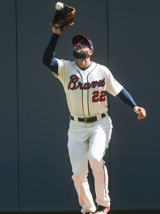 Atlanta Braves right fielder Nick Markakis catches a fly ball off the bat of Miami Marlins' Tyler Moore during the ninth inning of a baseball game, Sunday, Aug. 6, 2017, in Atlanta. (AP Photo/John Amis)