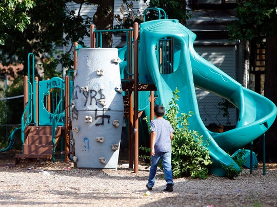 A boy walks towards playground equipment with graffiti behind 131 Second Street in Lakewood Friday morning, August 26, 2016.