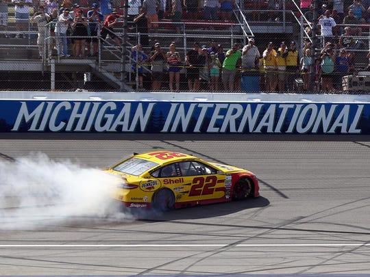 Joey Logano (22) does a burnout after winning the 2016