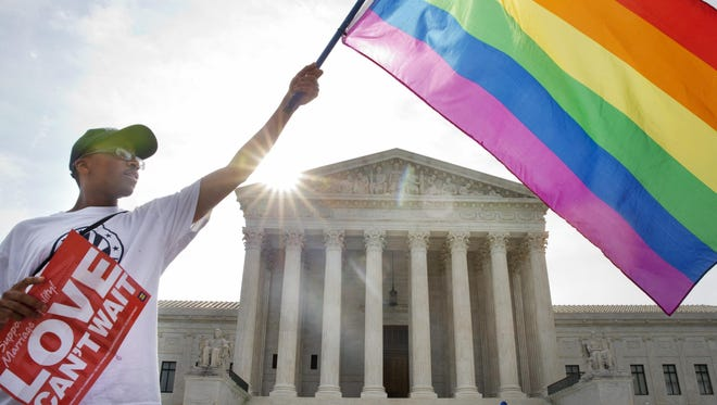 Carlos McKnight of Washington waves a flag in support of gay marriage outside of the Supreme Court in Washington on June 26, 2015.