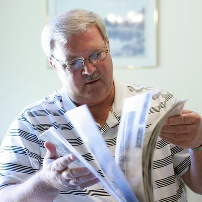 Steve Felker, of Newark, flips through a visual journal