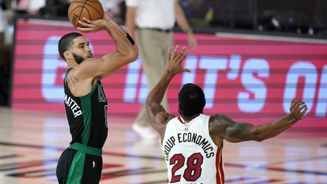 Boston Celtics forward Jayson Tatum attempts a shot as Miami's Andre Iguodala defends during the second half of Tuesday's first game of the Eastern Conference finals in Lake Buena Vista, Fla.