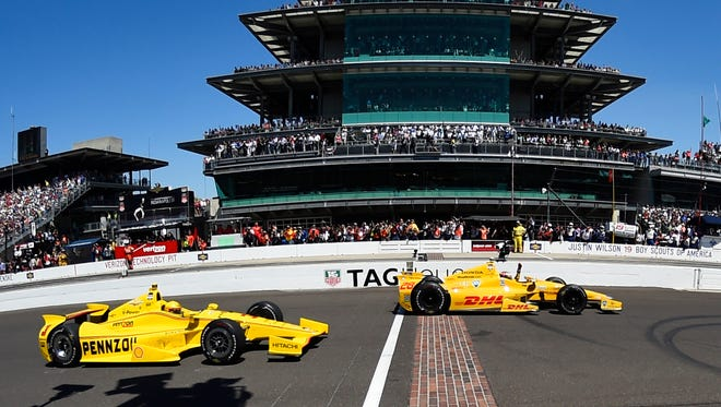 Ryan Hunter-Reay, right, crosses the start/finish line in front of Helio Castroneves to win the 2014 Indianapolis 500 at Indianapolis Motor Speedway.