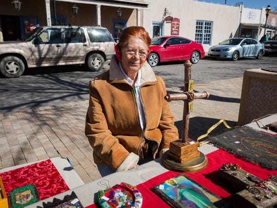 """Artist Mona Puente sits at her booth at Mesilla's """"For"""