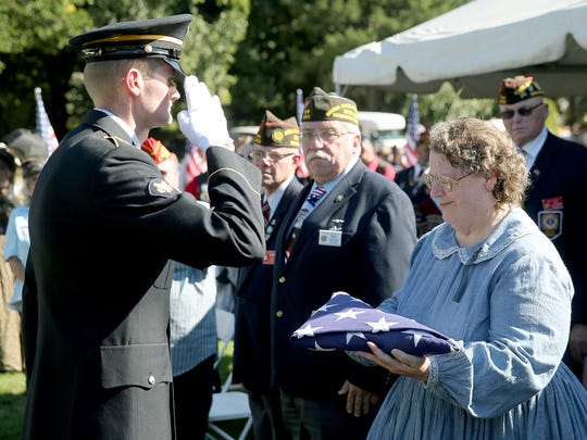 Loretta-Marie Dimond, of Kent, is presented with the flag of private Zachariah M. Stucker at the Retsil Veterans Home Cemetery on Thursday.
