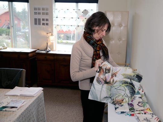 Karen Chaussabel, a Bainbridge artist and a designer with The Design Lab, looks over fabric samples.