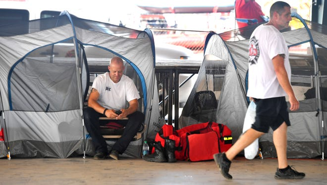 Scott Ellis of Brentwood Fire and Rescue smiles as he catches up with family members via email as he and other members of the Tennessee task force stage at the Ft. Bend Fairgrounds awaiting assignmentsFriday Sept. 1, 2017, in Houston, TX