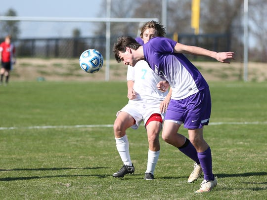 3 Trinity's Nick Taylor heads the ball away from USJ's Charles Campbell Mond.JPG