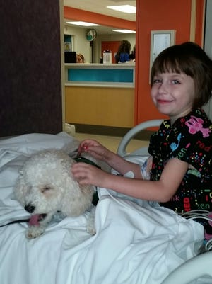 Natalie Davis visits with therapy dog Lucky a few days after surgery.