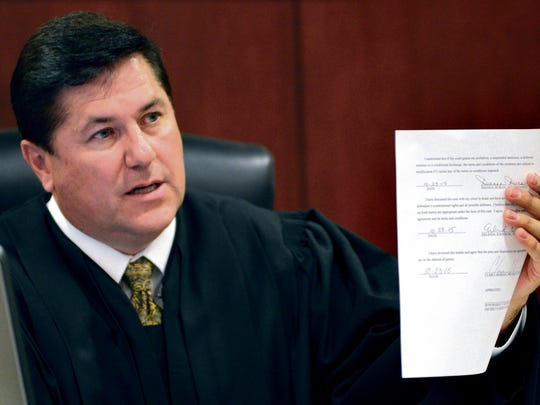 District Court Judge Glenn Ellington holds up a plea agreement page signed by former New Mexico Secretary of State Dianna Duran to confirm that Duran signed and fully understood all the elements of the plea Friday in Santa Fe.
