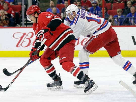 New York Rangers' Kevin Hayes (13) and Carolina Hurricanes' Trevor van Riemsdyk (57) chase the puck during the first period of an NHL hockey game in Raleigh, N.C., Saturday, March 31, 2018. (AP Photo/Gerry Broome)