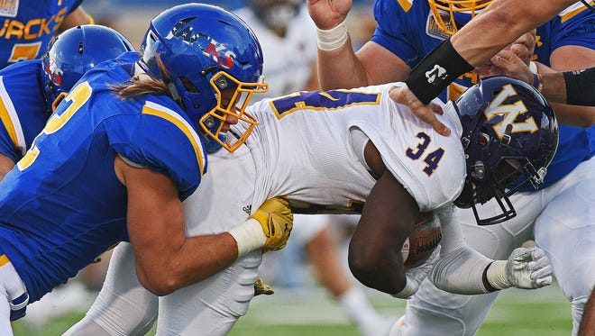 Western Illinois' Steve McShane (34) is brought down by SDSU's Christian Rozeboom (2) during a game Saturday, Oct. 1, 2016, at Dana J. Dykhouse Stadium on the South Dakota State University campus in Brookings, S.D.