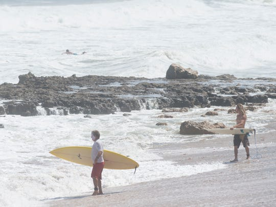 Surfers attempt to take on the waves soon after high tide Monday, Sept. 25, 2017 at Chastain Beach on South Hutchinson Island near Stuart. With Hurricane Maria churning offshore, waves on Florida's east coast reached 7 to 8 feet, with a high surf advisory and high rip current risk, according to the National Weather Service.