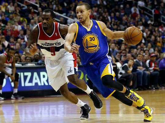 Golden State Warriors point guard Stephen Curry (30) dribbles the ball as Washington Wizards point guard John Wall (2) defends in the fourth quarter at Verizon Center. The Warriors won 112-96.