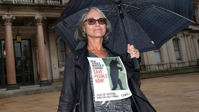 "A woman holds a sign with a bear near the Statehouse in Trenton, N.J. The death of a black bear presumed to be ""Pedals"" who walked upright on its hind legs due to an injury, is now serving as a rallying cry for those opposed to New Jersey's bear hunt."