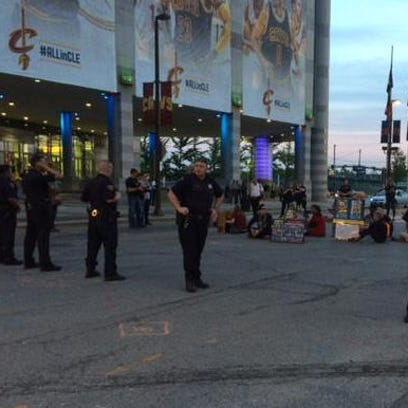 Small group of protesters sitting outside The Q