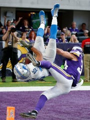 Golden Tate flips into the end zone past Vikings safety Andrew Sendejo for a a 28-yard TD in OT, Nov. 6, 2016, in Minneapolis. The Lions won 22-16.