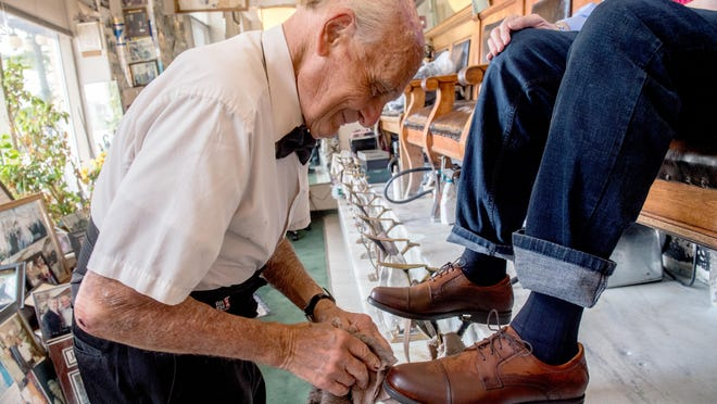 George Manias begins the shoeshining process for a client Thursday at George's Shoeshine and Hatters, 101 NE Adams St., in Downtown Peoria. Manias has finally returned to work after nearly three months off due to the coronavirus pandemic.
