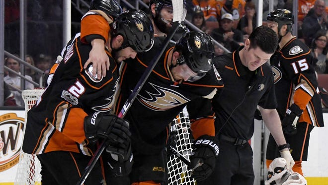 Anaheim Ducks defenseman Cam Fowler is assisted off the ice against the Calgary Flames.
