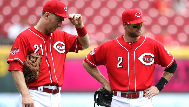 The Reds' Todd Frazier, left, and Zack Cozart wait for relief pitcher Burke Badenhop to warm up during the 7th inning  Wednesday at Great American Ball Park.