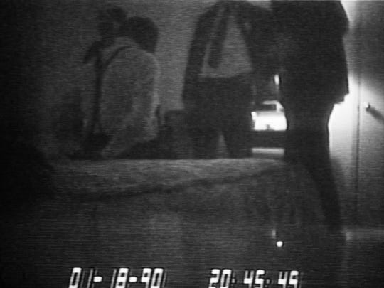 FILE - This file frame from a black-and-white FBI videotape shows FBI agents standing over a handcuffed District of Columbia Mayor Marion Barry, sitting on bed on Jan. 18, 1990. Barry, who staged a comeback after a 1990 crack cocaine arrest, died early Sunday morning Nov. 23, 2014. He was 78. (AP Photo/Barry Thumma)
