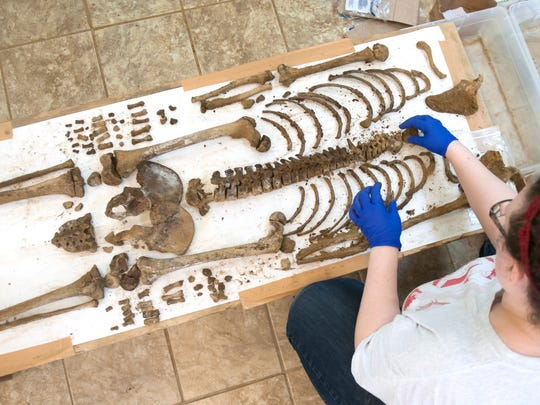 Allison Grunwald, an osteologist from Cherry Hill lays out bones from one of the coffins discovered at a construction site in Old City, Philadelphia, as the remains are fully dug from their coffins and examined at a facility in Burlington County.  07.17.17
