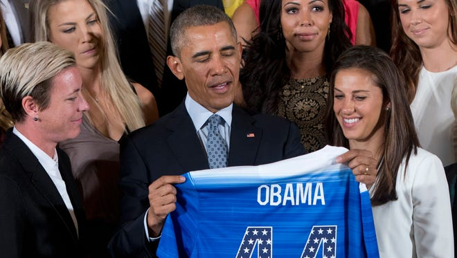President Barack Obama receives a soccer jersey as he welcomes the U.S. Women's National Soccer Team, including Carli Lloyd (right) in the East Room of the White House in Washington during a ceremony to honor the team and their victory in the 2015 FIFA Women's World Cup.