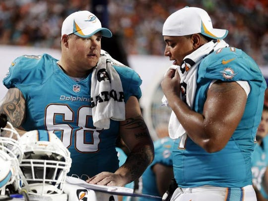 Richie Incognito (68) and tackle Jonathan Martin (71) look over plays during an NFL preseason game.