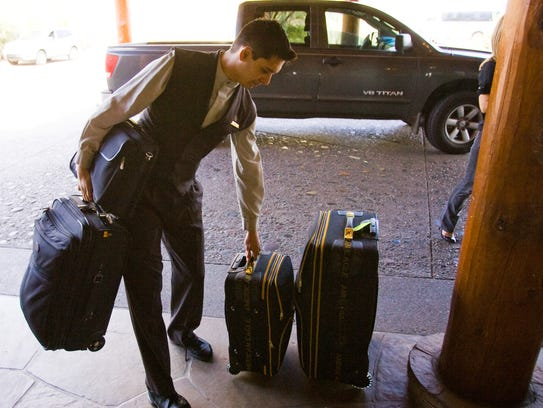 Bellhop Tim Gonzales  brings in luggage at the Four