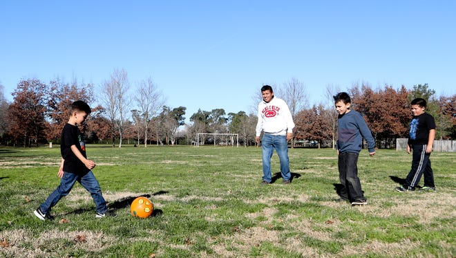 Ricky Vega, from left, plays soccer with his dad, Ricardo Vega, Jose Ponce, and brother, Bradley Vega, under a blue sky Wednesday at Enterprise Community Park in Redding.