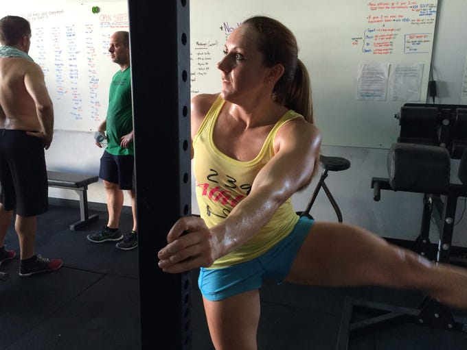 Sarina Woodworth stretched before a workout at CrossFit 239 in Fort Myers Tuesday. Woodworth is one of four locals who qualified to compete in the CrossFit Gamesâ?? South East Regional which starts Friday in Jacksonville.