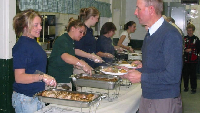 LaSalle Township grower John Mathe fills his plate with pork, kielbasa and salisbury steak at the 45th Annual Monroe County Agriculture Banquet at the 4-H Activity Center in 2006. Members of the 4-H Terra Quest Club, Milie Lennard (from left), Kellie Masserant and Emilie Chandonnet, served the meal as a fund-raiser for the club to take a trip to Tennessee in the spring.