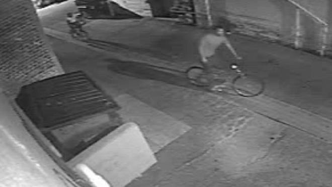 A suspect rides his bike in an alley behind Velouria Records off Main Street.