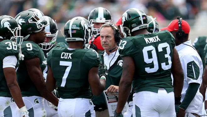 Michigan State head coach Mark Dantonio talks with his players during second half action against Air Force on Saturday, September 19, 2015 at Spartan Stadium in East Lansing Michigan.