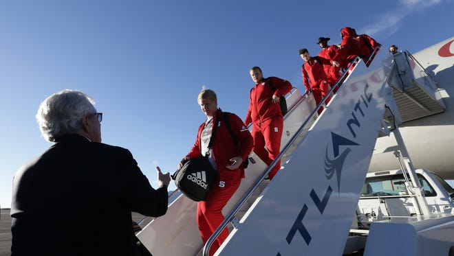 Hyundai Sun Bowl Football Committee Chairman John Folmer greets North Carolina State football players as they deplane Monday at Atlantic Aviation.