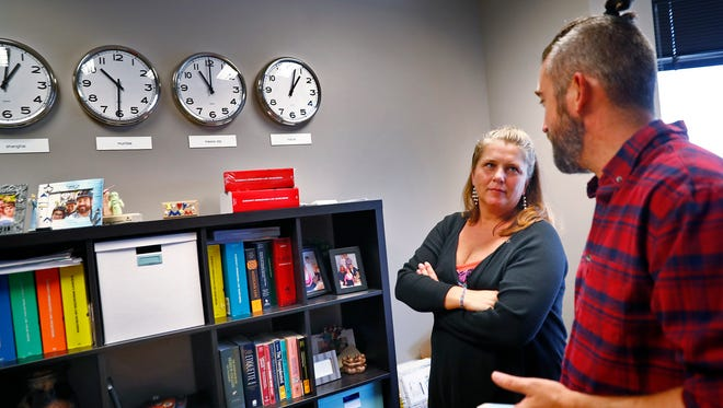 Sarah Burrow, left, and her husband Brendan Burrow talk in Sarah's Lewis Kappes law firm office, in downtown Indianapolis, Tuesday, July 10, 2018.  Sarah is an immigration attorney with the firm, and the couple just returned from doing volunteer work with the CARA Pro Bono Project, working with detainees in detention near the Mexico/U.S. border.